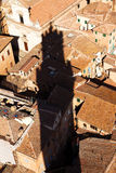 Towering shadow. Shadow from the Torre del Mangia on the roofs of the lower houses in Siena, Italy Stock Photography
