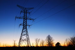 Towering Skyline. A large hydro tower in the foreground and more on the skyline in the setting sun. The last of the sun's rays are giving way to the oncoming Stock Image