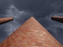 Towering Smokestacks with Storm Sky. Towering brick smokestack against a dark storm sky Royalty Free Stock Photos