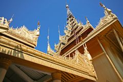 The golden and shimmering spires of a Burmese Palace in Mandalay, Myanmar. Towering spires of gold on the roof of a palace in Burma Stock Photos