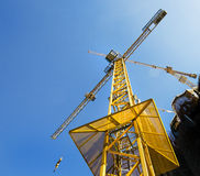 Towering yellow construction crane. Point of view shot underneath this tall yellow crane on a construction site. Building and and machinery at work Royalty Free Stock Image