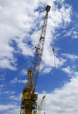 A Towering Yellow Crane Against a Blue and White Sky Stock Image