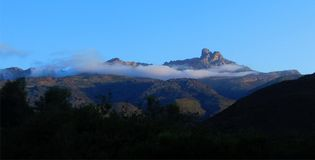 Towerkop Mountain - Ladismith. The Towerkop mountain encircled by a string of clouds like a scarf in the early morning sunlight.  Blue skies and green trees Royalty Free Stock Photography