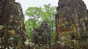 Towers of the ancient temple with stone faces. Cambodia, Bayon. Video 1080p - Towers of the ancient temple with stone faces. Cambodia, Bayon stock video footage
