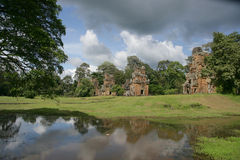 Towers of Angkor and pond. Ruined towers of ancient Angkor in Cambodia Royalty Free Stock Images