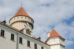 Towers of beautiful restored white castle with red tiles and blue sky in Czech Republic. Beautiful restored white castle with red tiles and blue sky in Czech Royalty Free Stock Photography