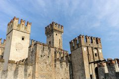 Old, knotty olive tree. Towers of the castle of Sirmione in Italy royalty free stock image