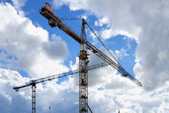 Towers cranes against a partly cloudy blue sky stock photo