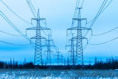 Towers of electric main in the winter countryside field on the background of blue sky and the forest with the wires royalty free stock photography