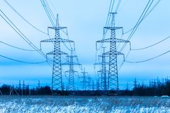 Towers of electric main in the winter countryside field on the background of blue sky and the forest with the wires stock image