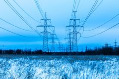 Towers of electric main in the winter countryside field on the background of blue sky and the forest with the wires royalty free stock image