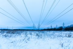 Towers of electric main in the winter countryside field on the background of blue sky and the forest with the wires stock photography