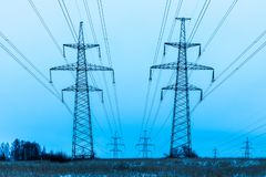 Towers of electric main in the winter countryside field on the background of blue sky and the forest with the wires royalty free stock photos