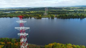 Towers of electricity transmission line against autumn landscape. Panorama white and red towers of overhead electricity transmission line against magnificent stock footage