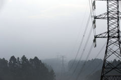 Towers of eletric power transmission in fog Stock Images