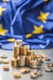 Towers with euro coins and flag of European Union in the background stock photo