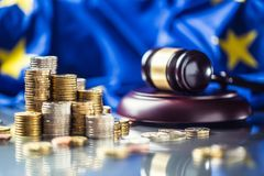 Towers with euro coins flag of European Union and justice hammer in the background. Currency court gavel money judge wooden law legal banknote business mallet royalty free stock images