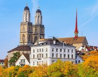 Towers of the Grossmunster cathedral in Zurich, Switzerland. Colorful trees and towers of the Grossmunster cathedral in the city of Zurich, Switzerland. The royalty free stock photos