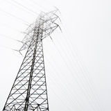 Towers of high voltage. Electrical tower of high voltage between light fog. Black and white Stock Photography