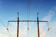 Towers and high-voltage wires against the blue sky. Electric net. S in the rays of the setting sun. Submission of eletricity in the city Royalty Free Stock Images