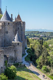 Towers of La Cite. Part of fortification of medieval city La Cite in Carcassonne with white peaks of Pyrenees stock images