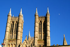Towers of Lincoln Cathedral. The towers on the facade of the amazing Cathedral of Lincoln, UK, in early eavening sun, the moon is in the distance stock photo