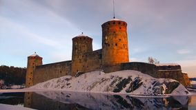 The towers of the medieval fortress of Olavinlinna in the setting sun on a March evening. Savonlinna, Finland. The towers of the medieval fortress of Olavinlinna stock footage