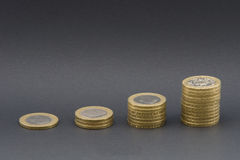 Towers of money. A shot of towers of £2 coins in a softbox isolated on grey Royalty Free Stock Images