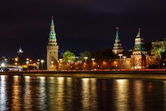 Towers of Moscow Kremlin with glowing reflection of night illumination on water surface of Moskva river stock image