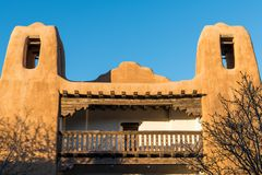 Towers of an old pueblo style adobe building with rustic, ornate wood beams and balcony in Santa Fe, New Mexico. Historic adobe building with two towers, ornate royalty free stock photos