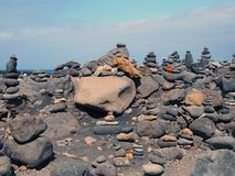 Towers of stacked pebbles and stones in different colours in a large arrangement on a black sand beach with blue sky Stock Photos