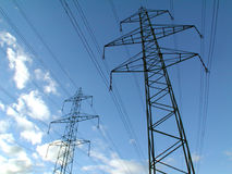 Towers of power. Power poles in front of a cloudy blue sky Royalty Free Stock Photos
