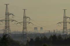 Towers of power lines in the pre-dawn fog Stock Images