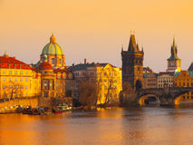 Towers of Prague Old Town and Charles Bridge over Vltava River illuminated by sunset Stock Photography