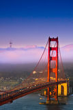 Towers, San Francisco, California. The warm light of sunrise mixes with coastal fog to illuminate the south tower of the Golden Gate Bridge and Sutro Tower in Stock Photos