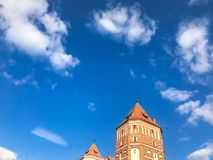 Towers and spiers of a high medieval stone old ancient beautiful castle against a blue sky stock photos