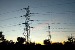 Towers supporting power lines in the twilight Royalty Free Stock Photos