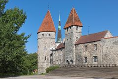 Towers of Tallinn City Wall and spire of St. Olaf`s Church, Estonia. Tallinn, Estonia. Loewenschede Tower and Nunnadetagune Tower Tower behind Nuns of the Royalty Free Stock Image