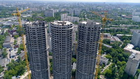 Towers under construction stand above residential and industrial buildings. Aerial view. Towers under construction stand above residential and industrial stock video