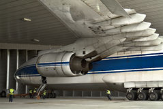 Towing aircraft in the hangar for trial launch engines-maintenance of aircraft at the airport in Leipzig. Towing the aircraft to the hangar for trial launch of stock photography