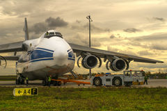 Towing aircraft Ruslan (Russia) after the service at the airport Leipzig (Germany) on a cloudy summer day Royalty Free Stock Image