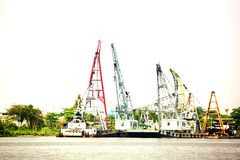 Towing boat or cargo ship with crane at riverside port royalty free stock photo