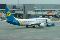 Towing Boeing 737 UR-PSR Ukrainian International Airlines on the Schiphol Airport royalty free stock photo