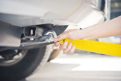 Towing car with towing rope. Hand holding yellow car towing strap with car, car towing royalty free stock images