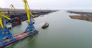 Towing cranes for containers. Large container ship pulled by tugboats. Top down aerial view. Container Cargo freight stock video footage
