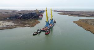 Towing cranes for containers. Large container ship pulled by tugboats. Top down aerial view. Container Cargo freight stock footage
