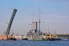 Towing cruiser Aurora. Towing the cruiser Aurora with its Parking lot near the College named Admiral Makarov on the Neva River under Kirov bridge for major royalty free stock photography