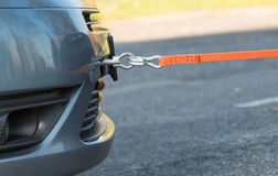 Towing hook and orange rope. Towing hook and tow rope assembled to a broken car stock photography