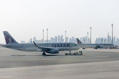 Towing Qatar aircraft to the parking lot by TUG Pushback tractor. stock photos