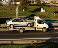 Towing service. Silver car, being towed, on a towing truck speeding on a highway Royalty Free Stock Photos